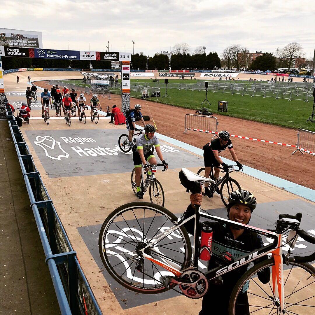 Fábio Miyake mostra a sua bicicleta Soul na chegada da prova Paris-Roubaix, no Velódromo de Roubaix, enquanto outros ciclistas cruzam a linha final