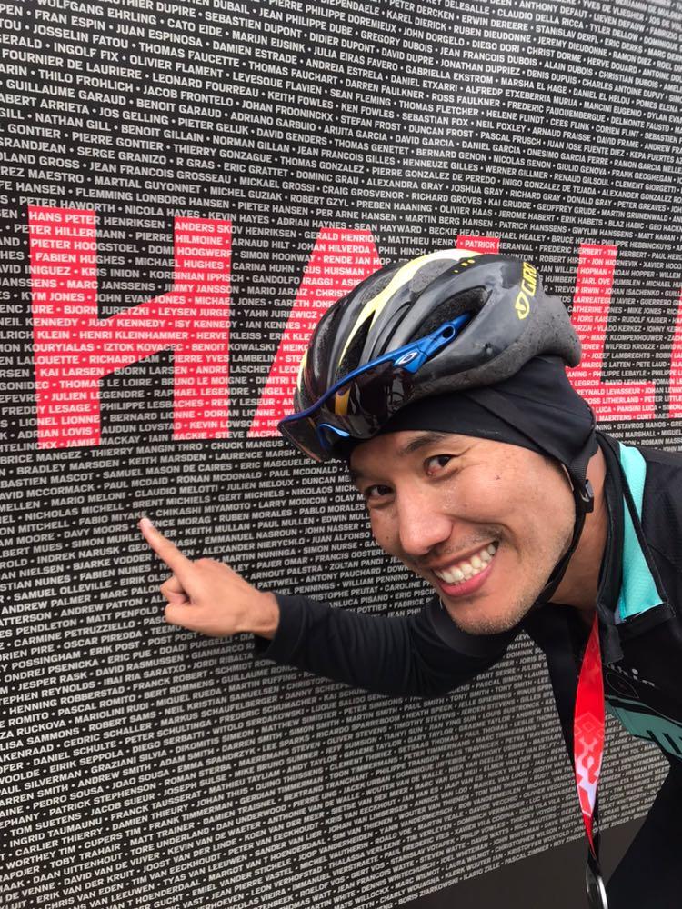 Fábio Miyake aponta para o seu nome em um banner da prova de ciclismo Paris-Roubaix