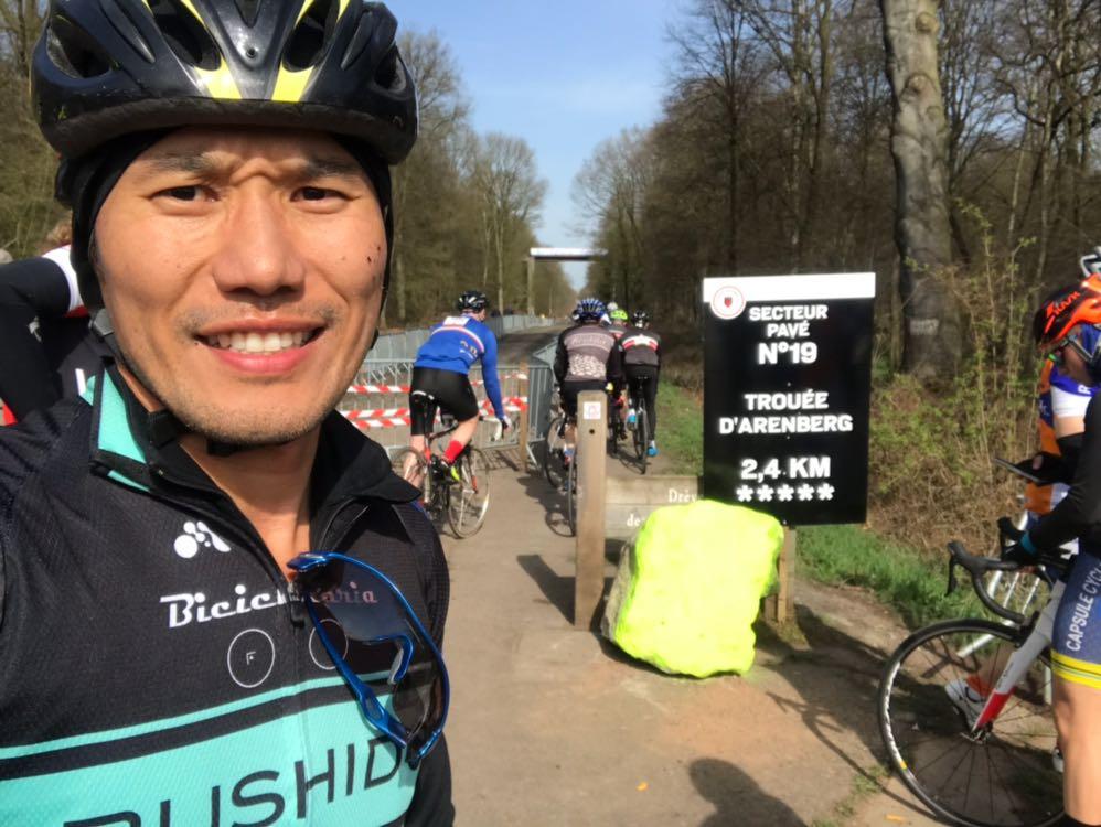 Fábio Miyake tira uma foto em frente a uma placa que indica um dos trajetos da Paris-Roubaix, na Floresta de Arenberg