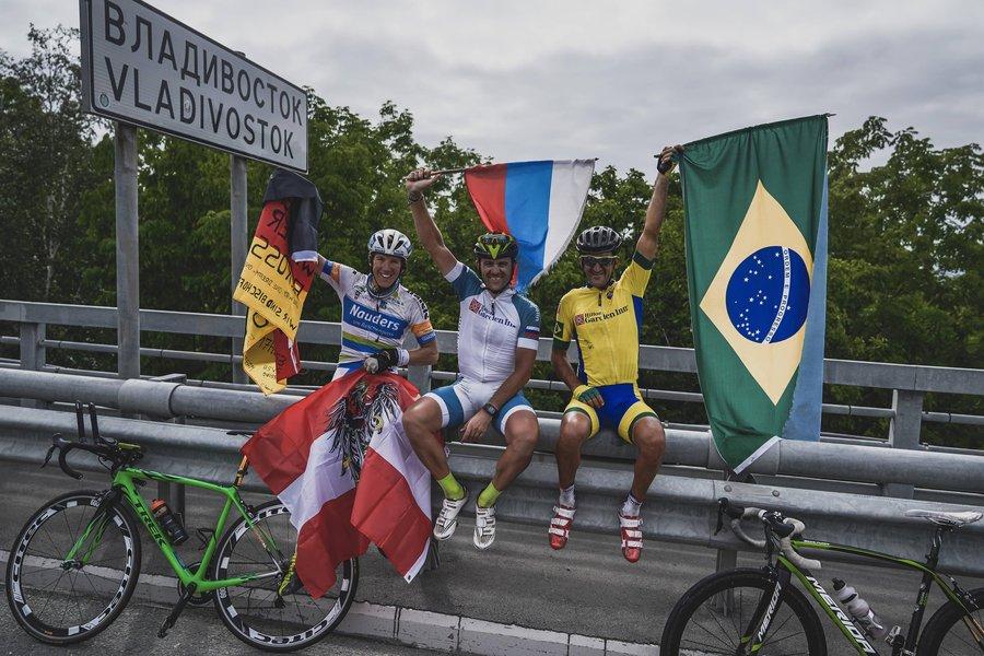 Mixirica exibe a bandeira do Brasil ao lado do russo Alexey Shchebelin e do alemão Pierre Bischoff em uma mureta após o fim do Trans-Siberian