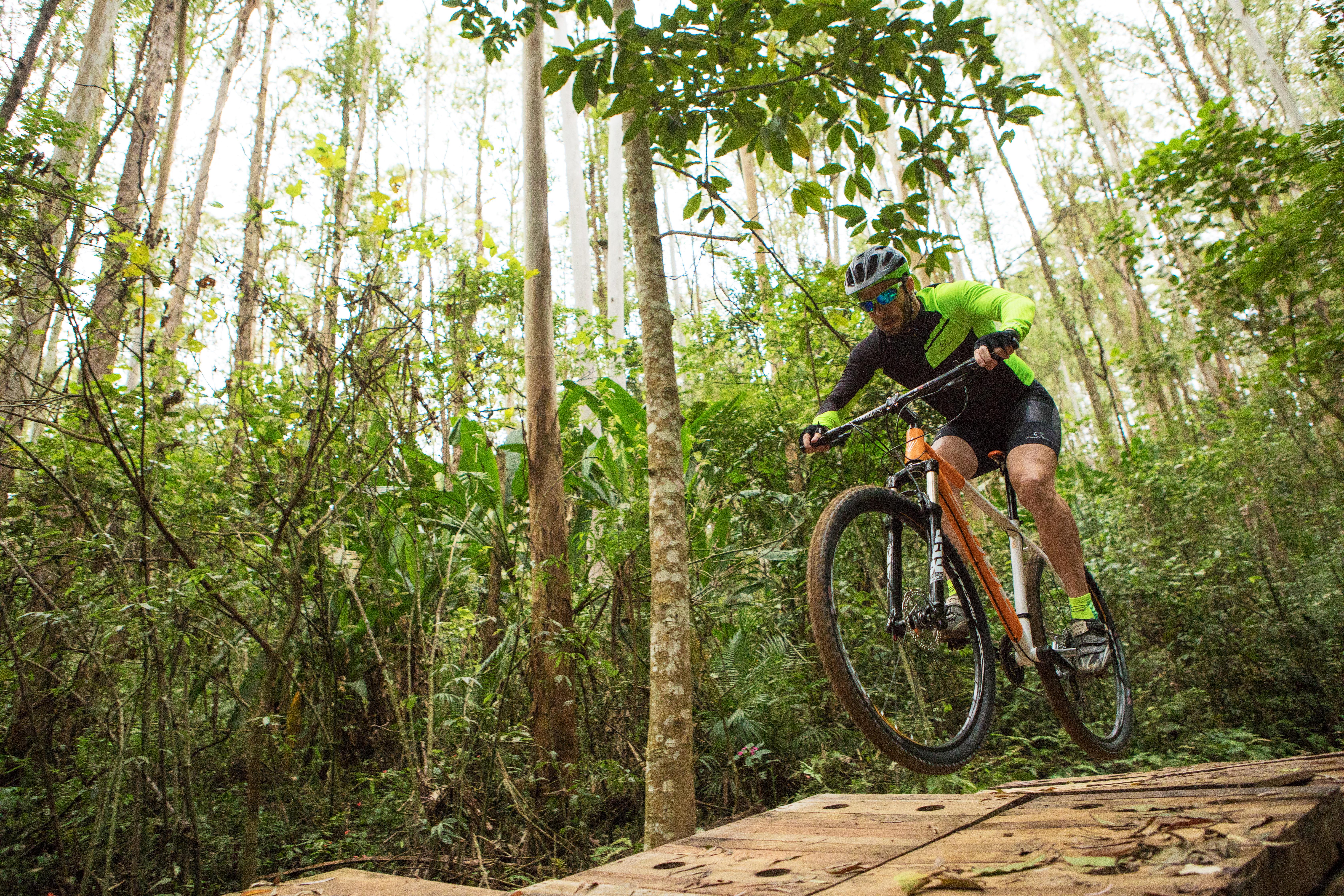 Ciclista salta um obstáculo com sua bicicleta no meio da mata