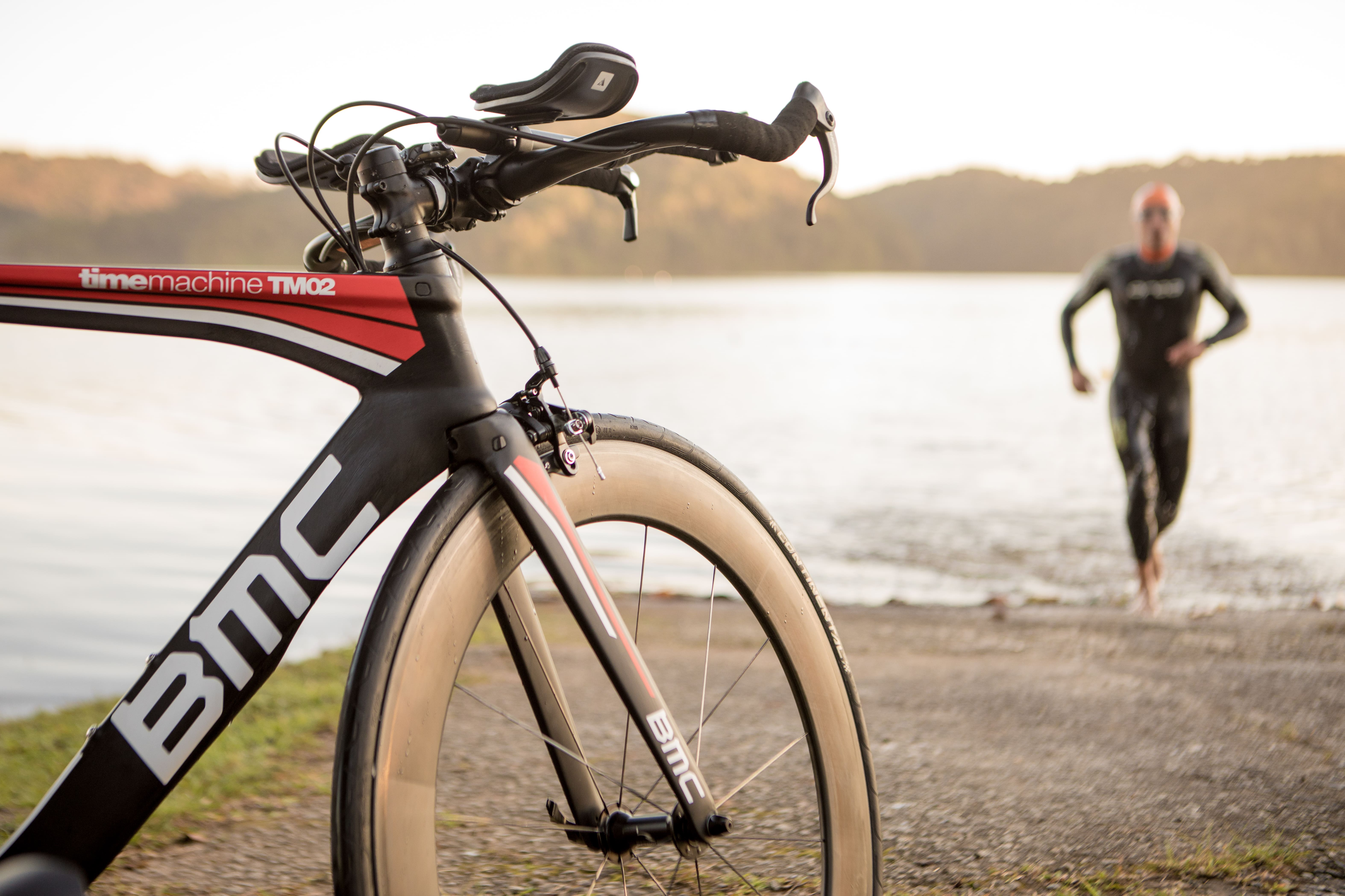 Modalidades de ciclismo: Atleta sai da água para pegar a sua bicicleta BMC