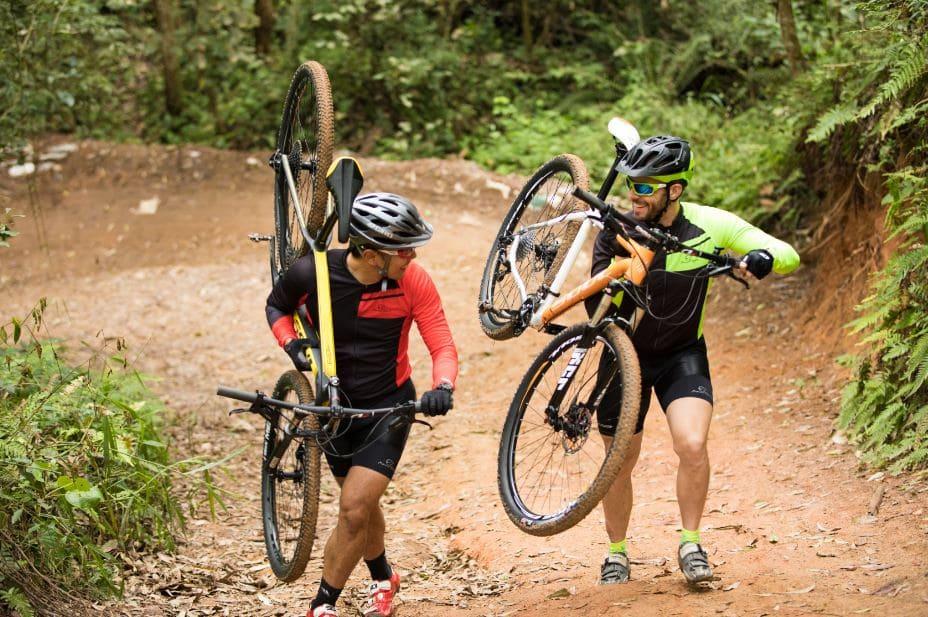 Dois ciclistas carregam suas bicicletas no ombro em uma estrada de terra