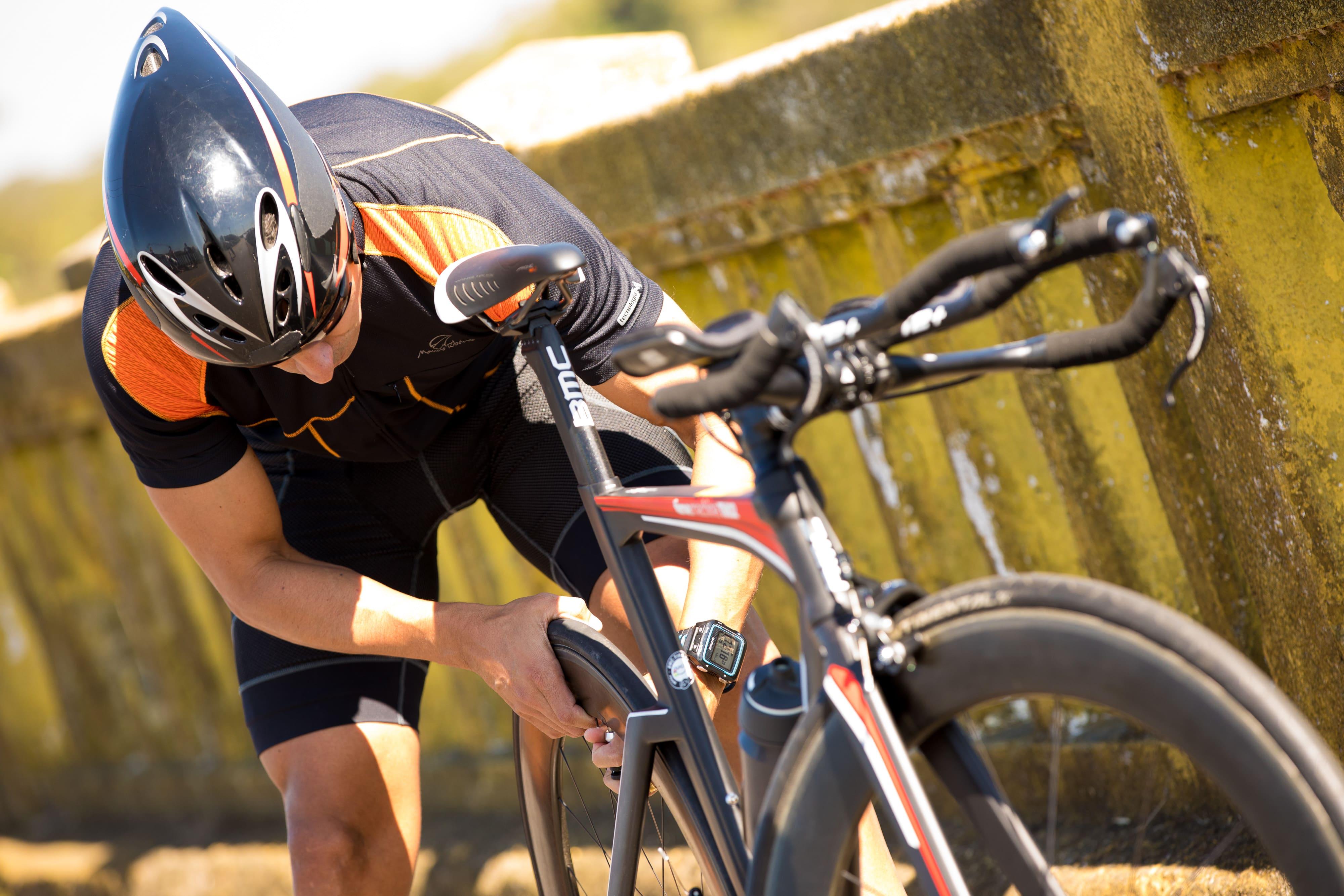 Ciclista enche o pneu da sua bicicleta no acostamento de uma estrada