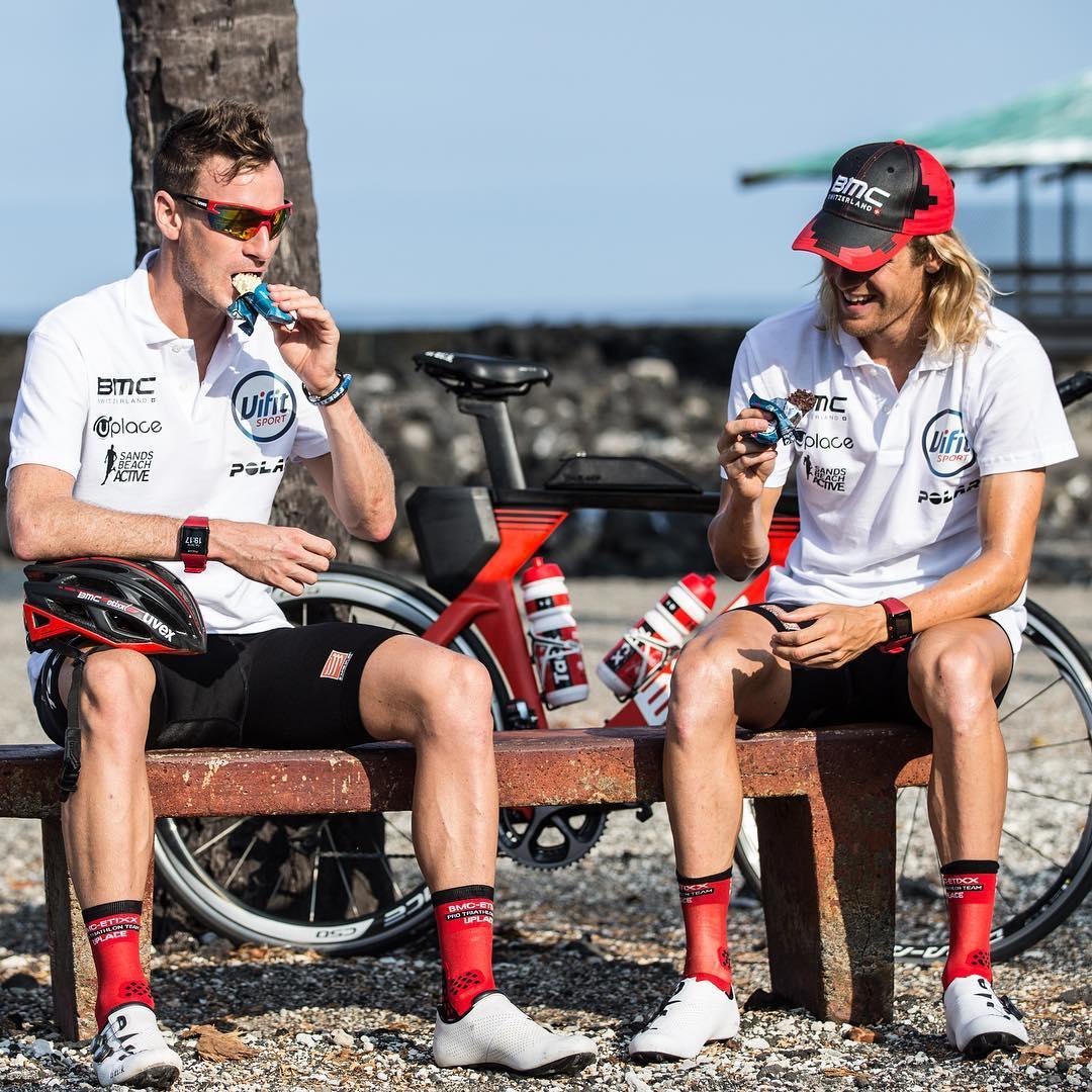 Nutrição no ciclismo: dois ciclistas da equipe de triatlo da BMC estão sentados em um banco comendo uma barra de cereal