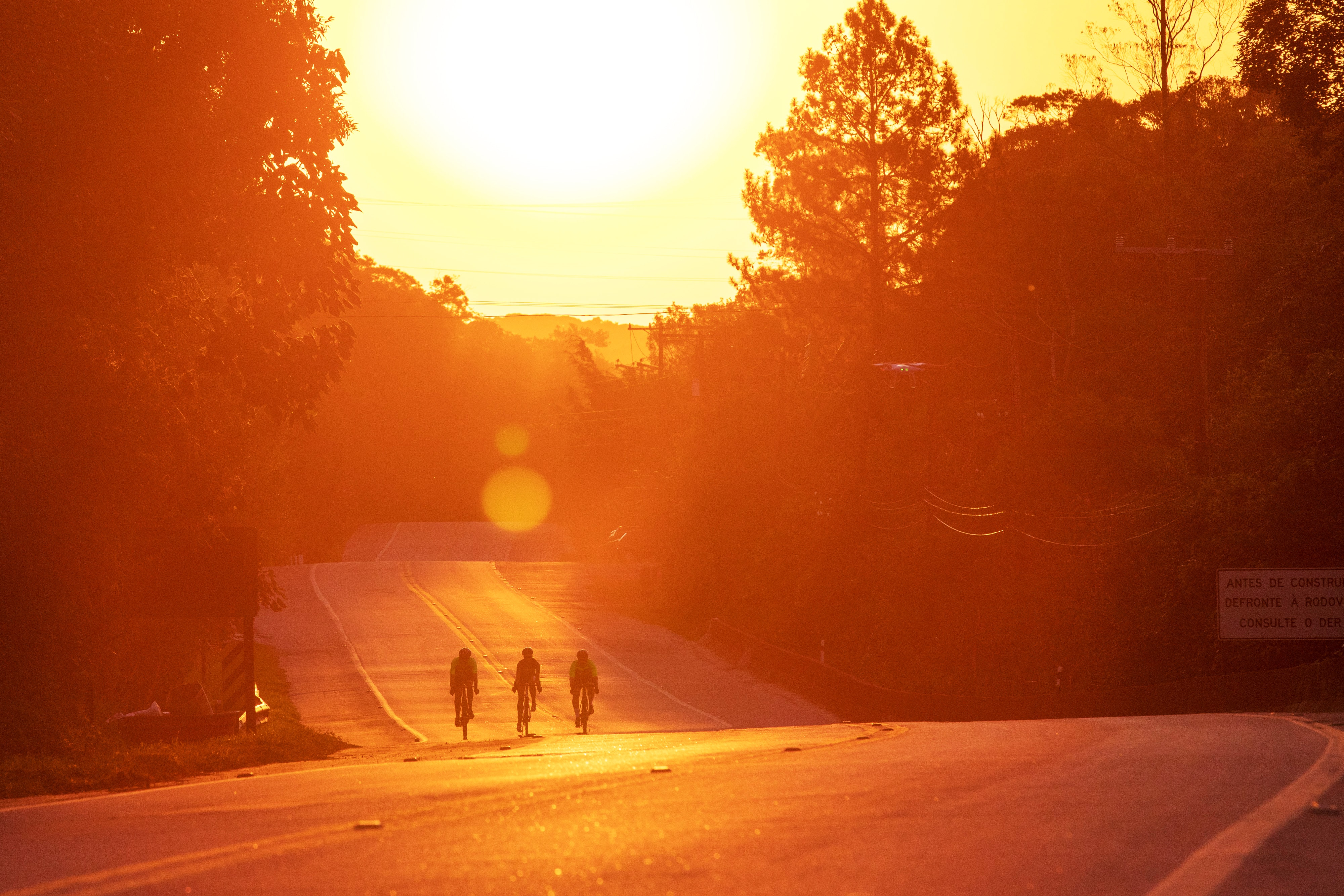 Pedalar no calor: três ciclistas pedalam em uma estrada enquanto o sol se põe