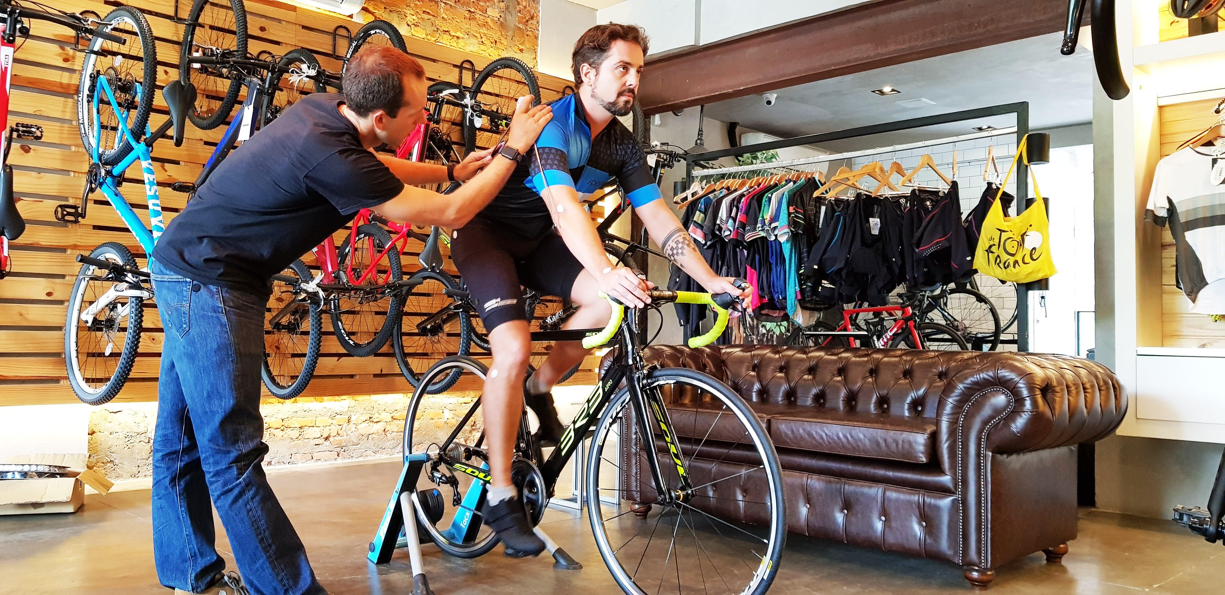 Cassio Cortes está sentado em sua bicicleta, a 3R3 Aero, da Soul Cycles, na loja, enquanto Igor Laguens tira as suas medidas para o bike fit