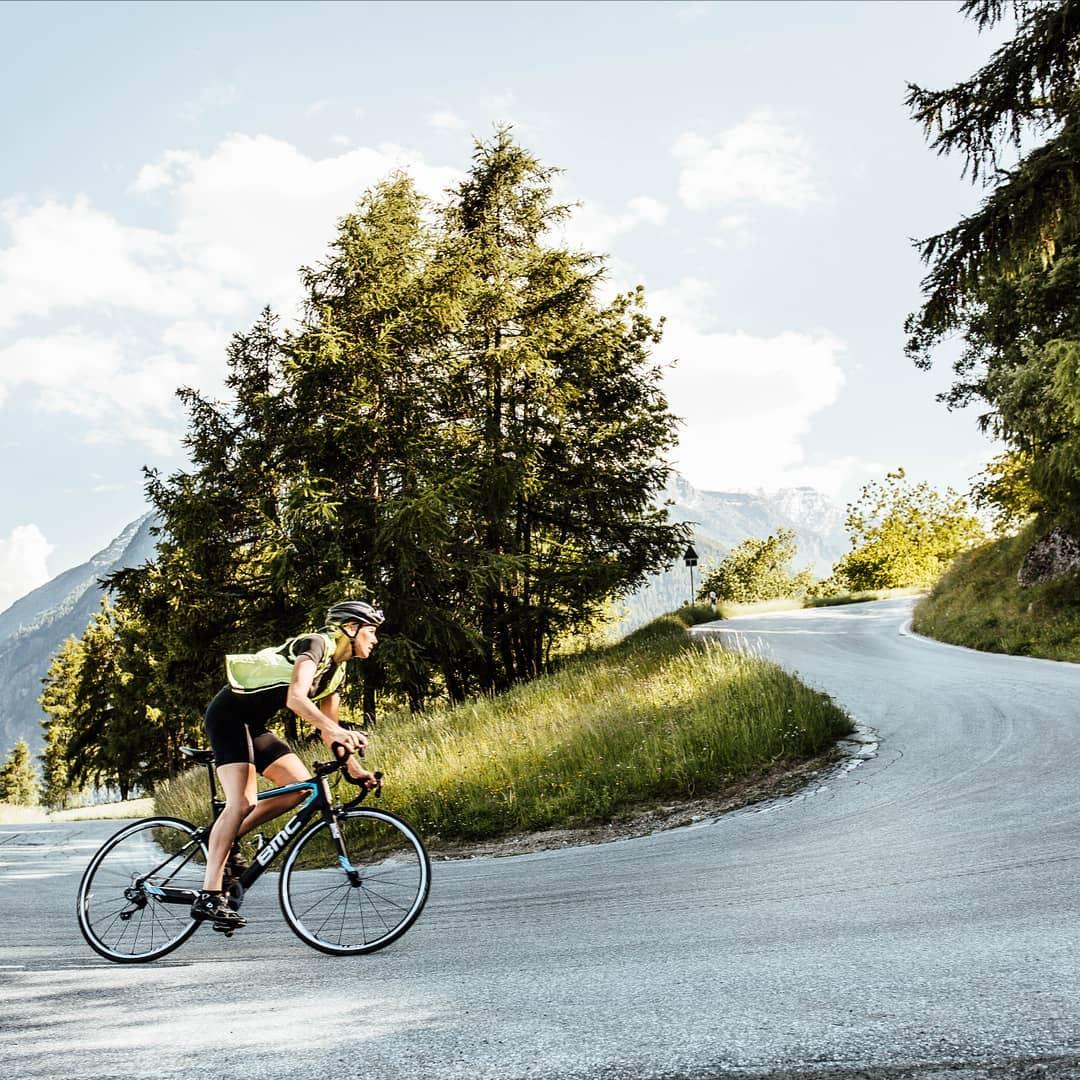 Pedalar em subida: uma ciclista com a sua bicicleta BMC pedala em uma subida