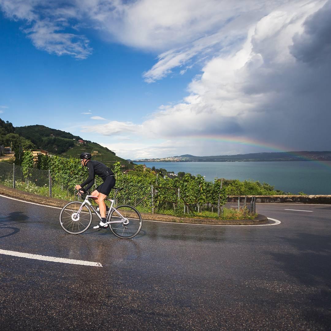 Ciclista encara uma subida com um arco-íris ao fundo