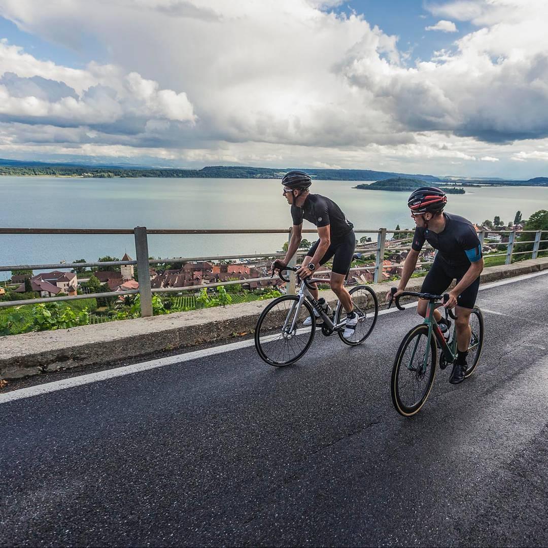 Dois ciclistas pedalam em uma subida enquanto observam a paisagem