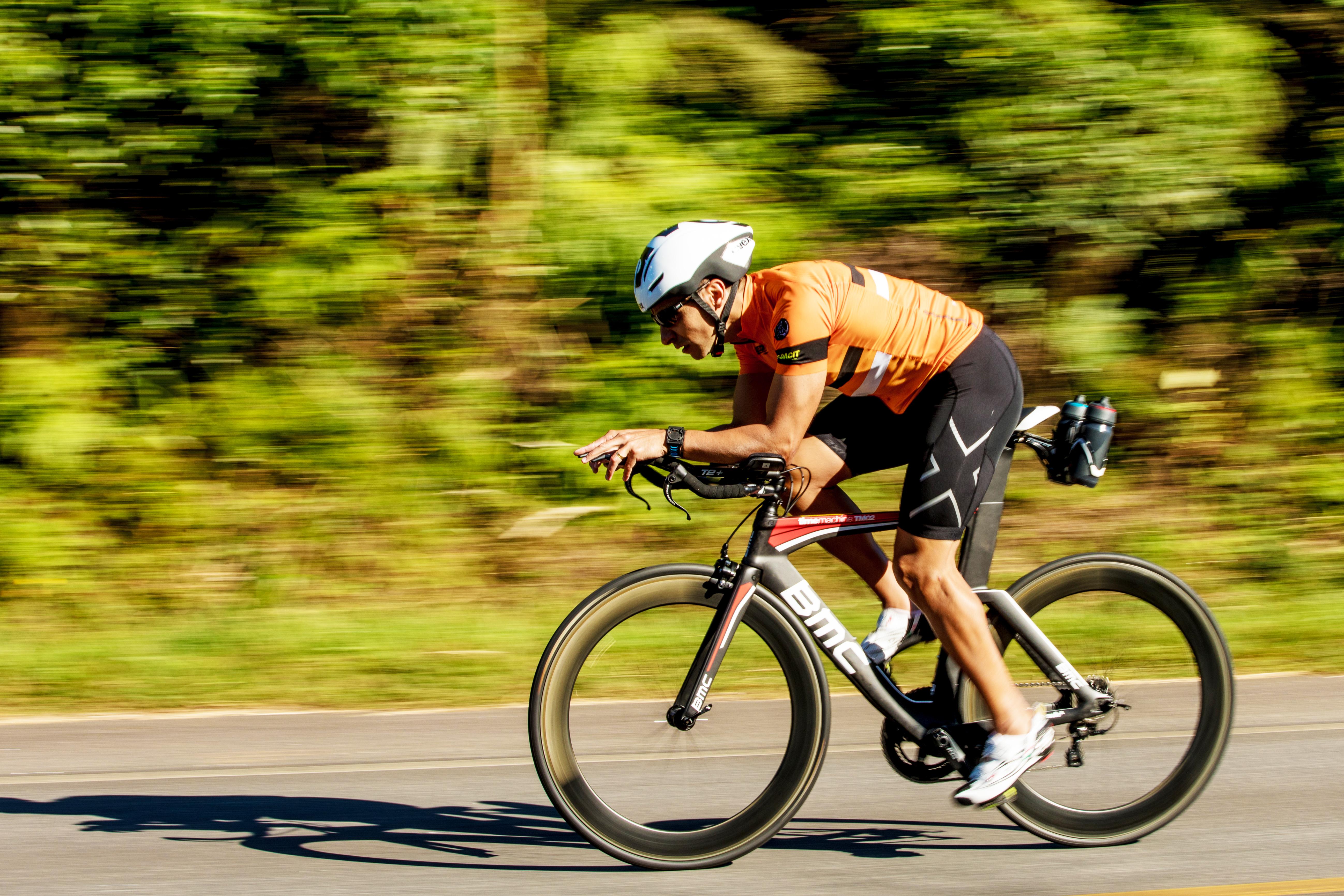Velocidade média no ciclismo: ciclista pedala uma bicicleta da BMC em uma estrada sob um sol forte